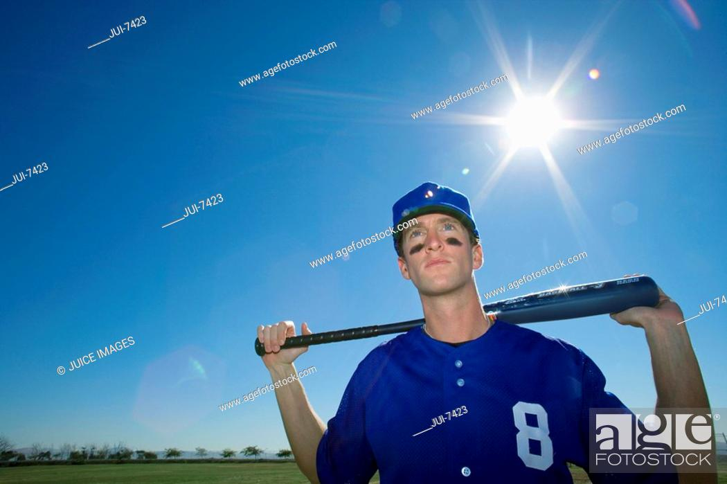 Stock Photo: Baseball player, in blue uniform and cap, standing on pitch with bat behind head, front view, portrait lens flare.