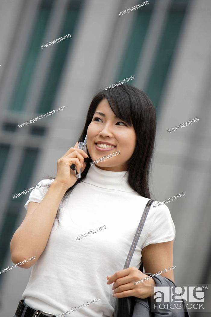 Stock Photo: A woman smiling as she converses on the mobile phone.