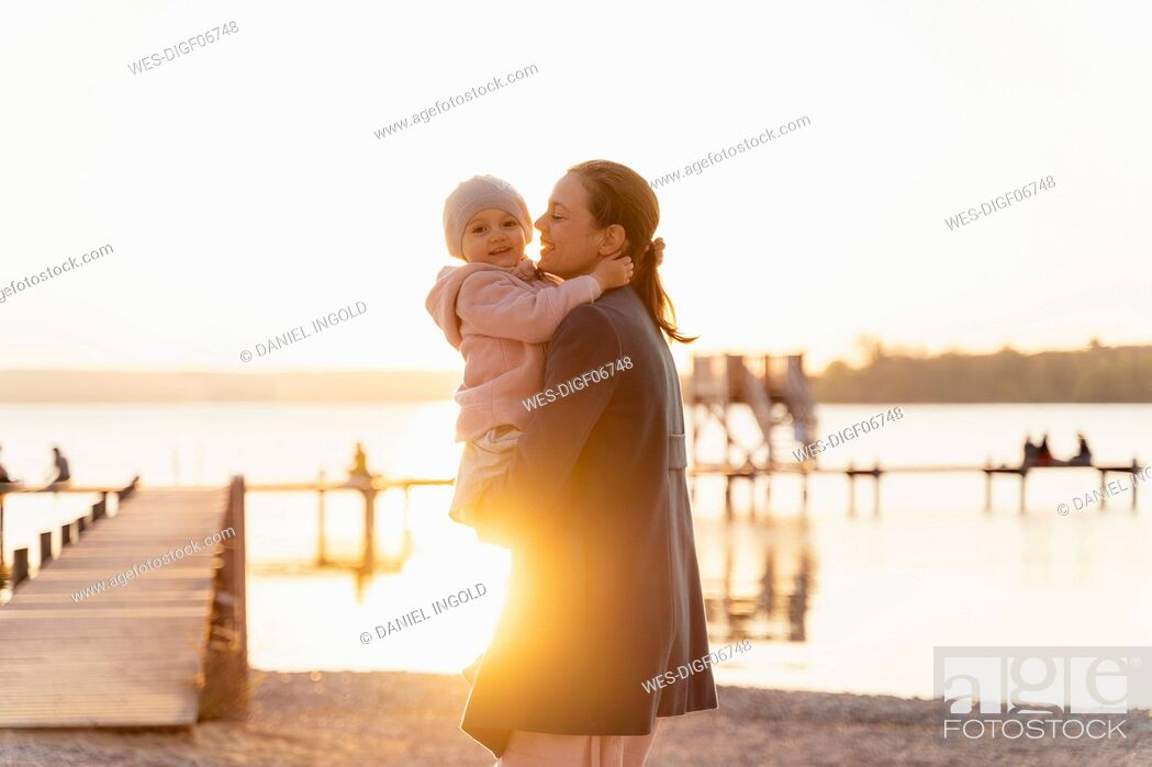 Stock Photo: Germany, Bavaria, Herrsching, mother carrying daughter at the lakeshore at sunset.