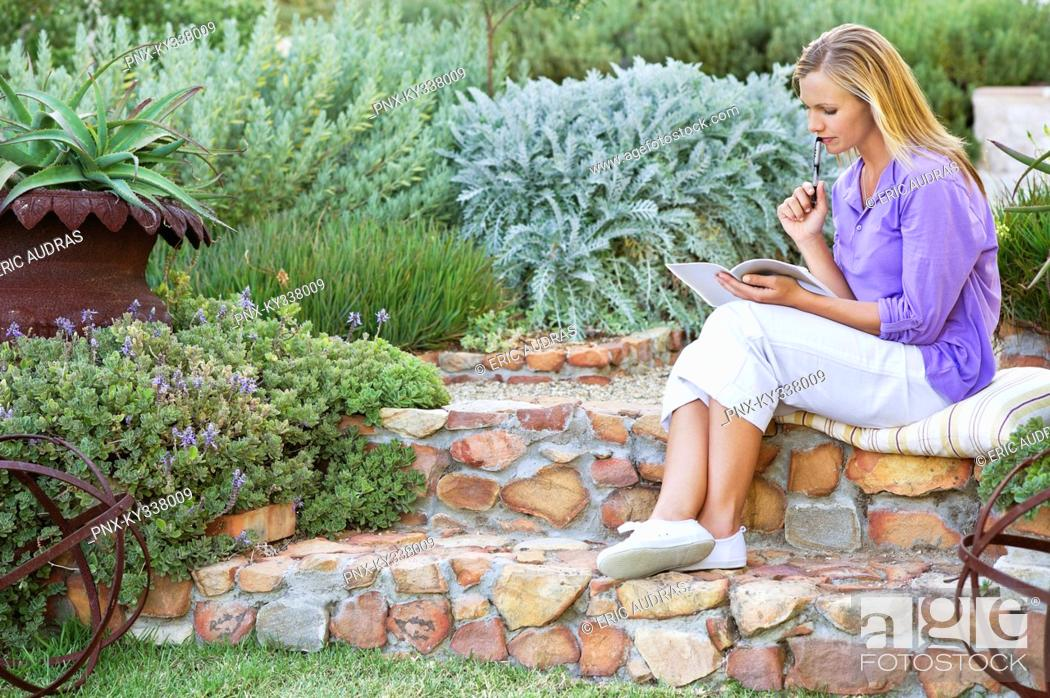 Stock Photo: Beautiful young woman reading book in garden.