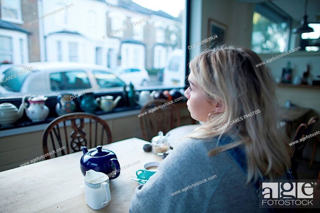 Stock Photo: Young woman sitting in cafe, cup of tea and teapot on table, looking out of window.