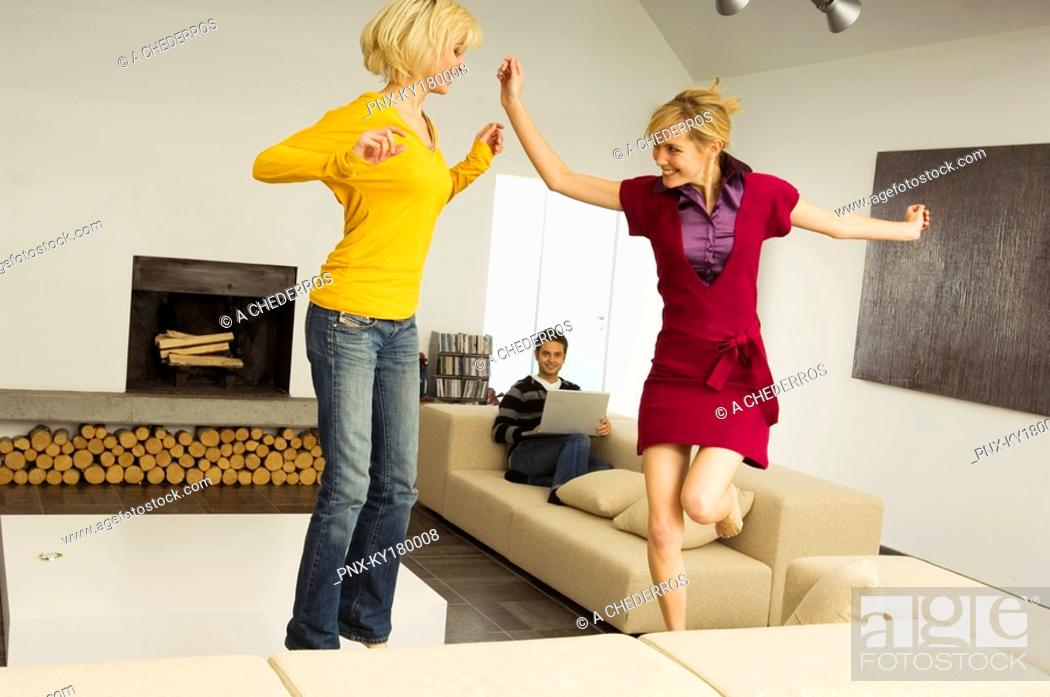 Stock Photo: Two young women dancing with a young man using a laptop in the background.