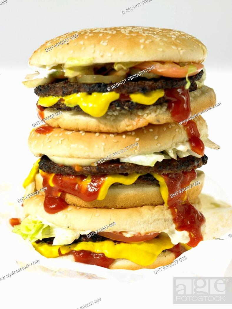 Stock Photo: Three beef burgers with toppings in take out packaging.