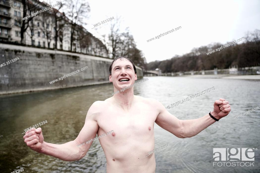 Stock Photo: ice bathing, man rejoicing after swimming in cold river Isar, Munich, Germany, in January during winter.