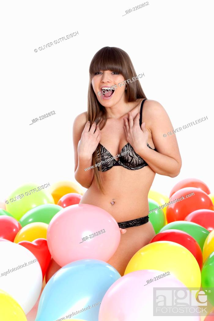 e82a7f0dc05 Stock Photo - Young woman wearing lingerie sitting between colourful  balloons and screaming with joy