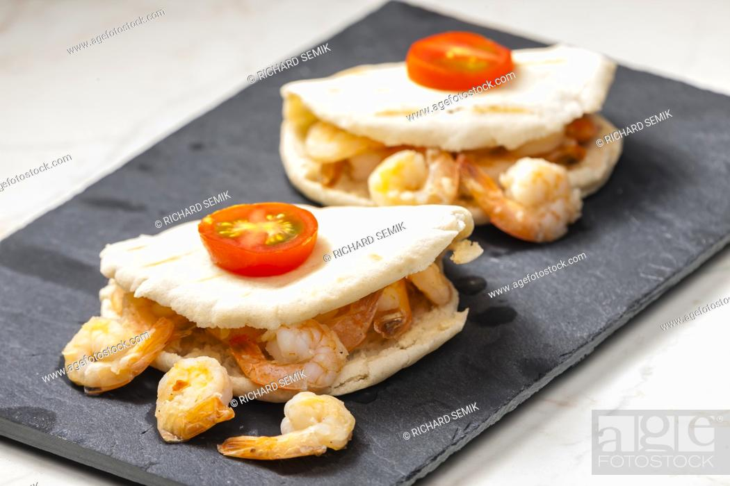 Stock Photo: pitta bread filled with shrimps and tomatoes.