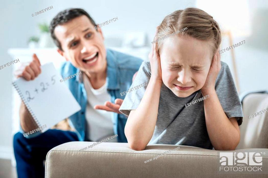 Stock Photo: Stupid. Outraged dark-haired young father holding and pointing at his daughters incorrect equation and shouting at her.