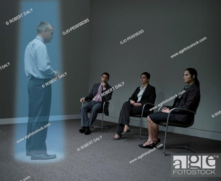 Stock Photo: Three businesspeople watching a hologram of a businessman.