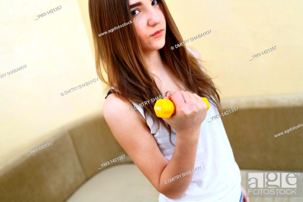 Stock Photo: Young woman wearing yellow exercise shirt doing arm curls looking at bicep.