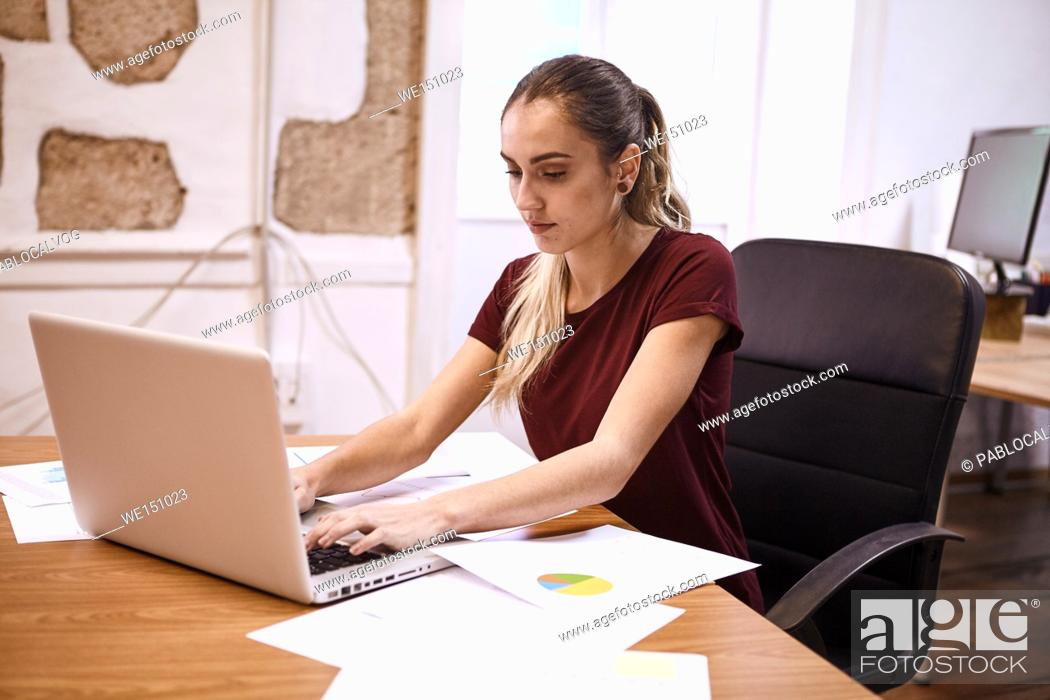 Stock Photo: Smart young business woman typing on her laptop with concentration with presentation notes with pie charts lying on her desk.