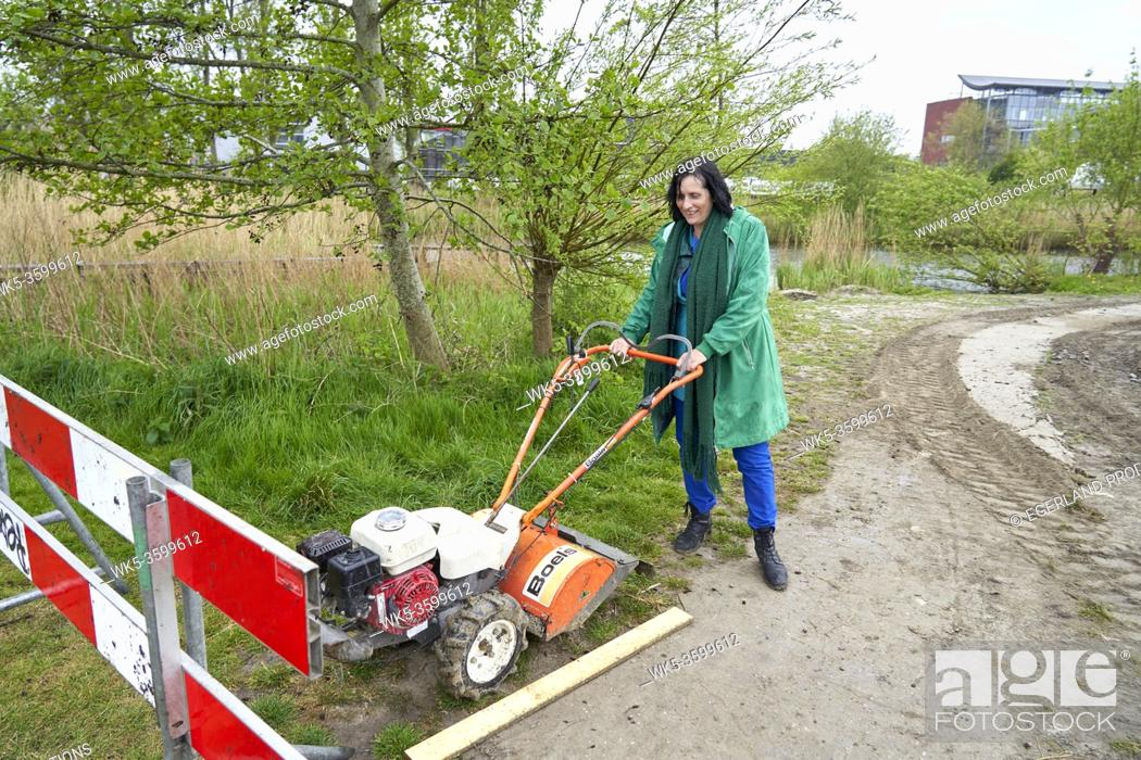 Stock Photo: woman with street work machine constructing bike lane to reduce environmental pollution and emissions.