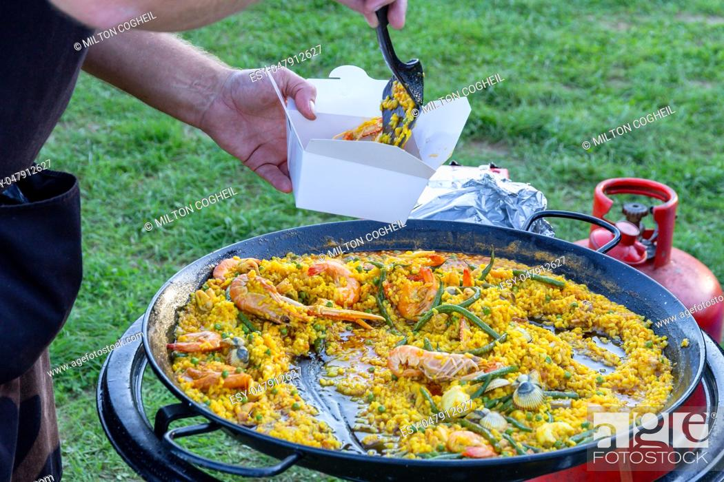 Stock Photo: A large pan of seafood paella being served outdoors.