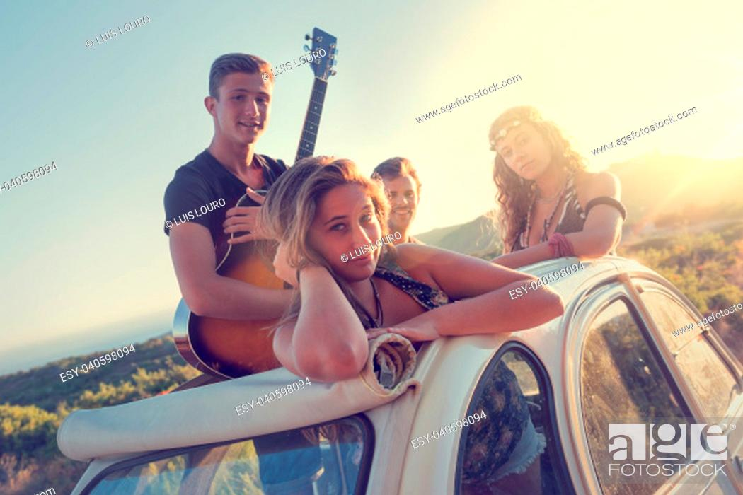 Stock Photo: Group of happy people in a car at sunset in summer.