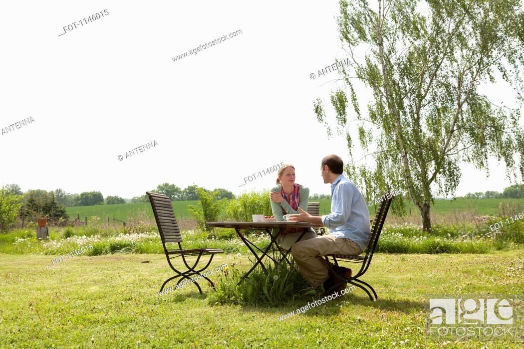 Stock Photo: A couple having breakfast in their backyard.