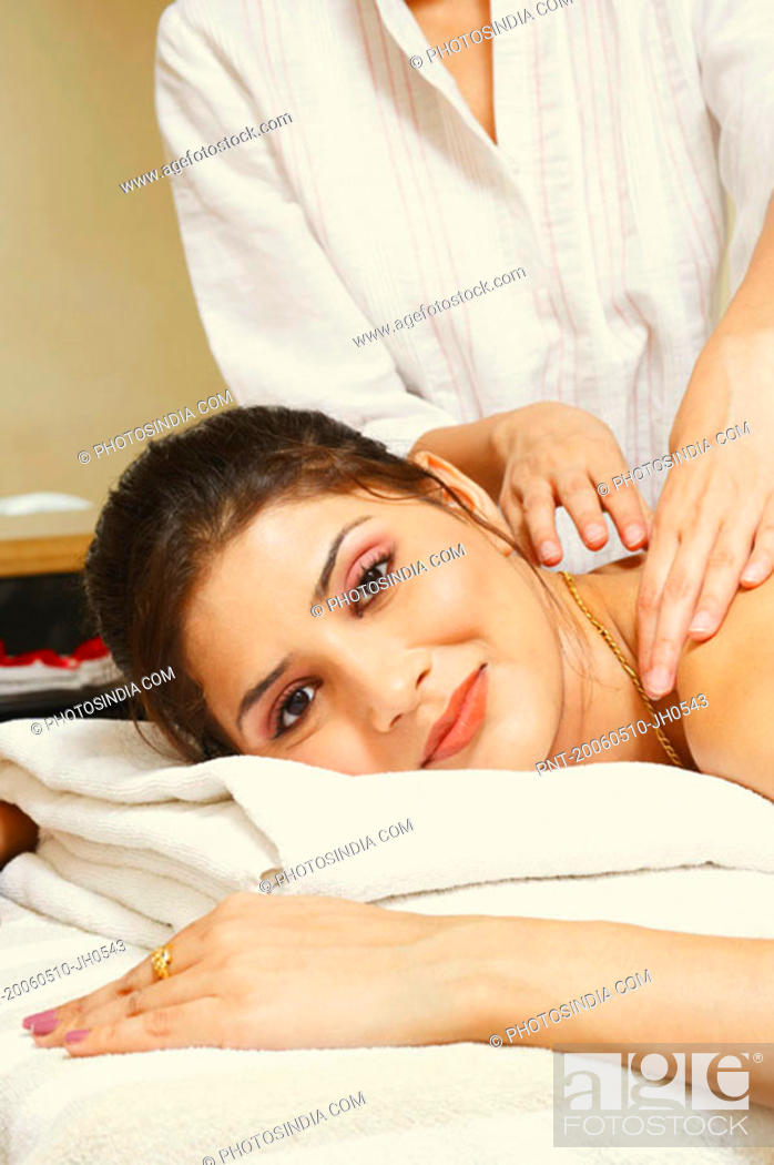 Stock Photo: Portrait of a young woman getting a shoulder massage from a massage therapist.