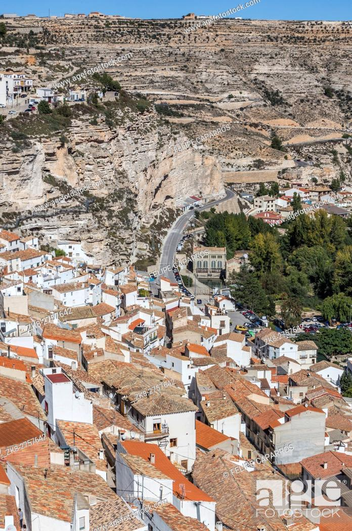 Stock Photo: Houses and roofs next to mountain limestone, view to the mountains of the river Jucar, take in Alcala of the Jucar, Albacete province, Spain.