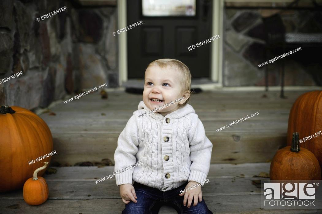 Stock Photo: Baby boy sitting on front porch with pumpkins looking up smiling.