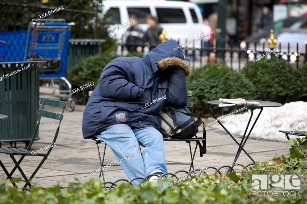 Stock Photo: Homeless man taking a nap in Bryant Park in New York City.