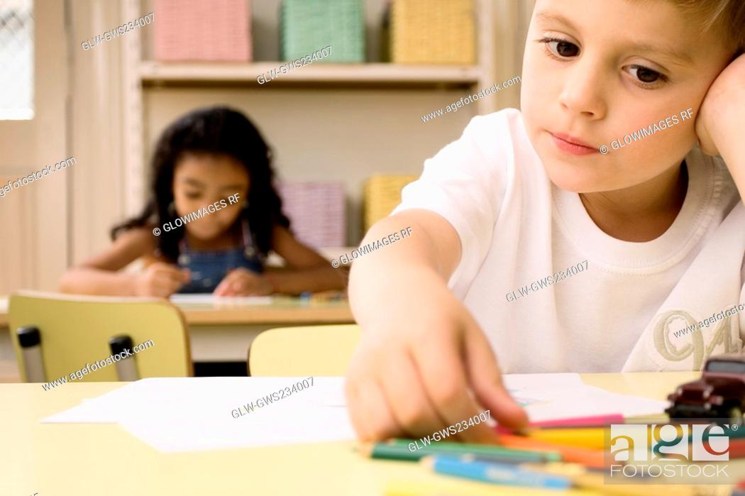 Stock Photo: School children drawing on sheets of paper in a classroom.
