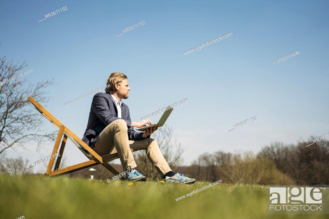 Stock Photo: Surface level view of businessman looking away while sitting with laptop on chair at park during sunny summer day.