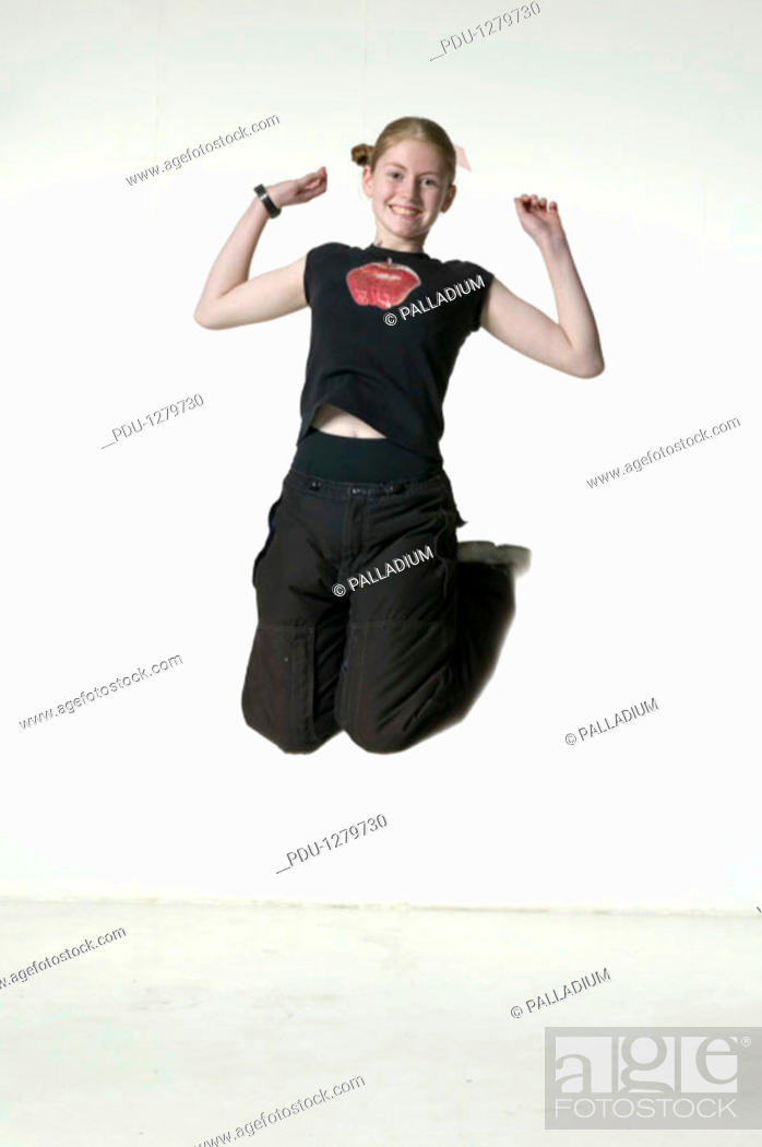 Stock Photo: Young woman jumping up with joy, portrait.