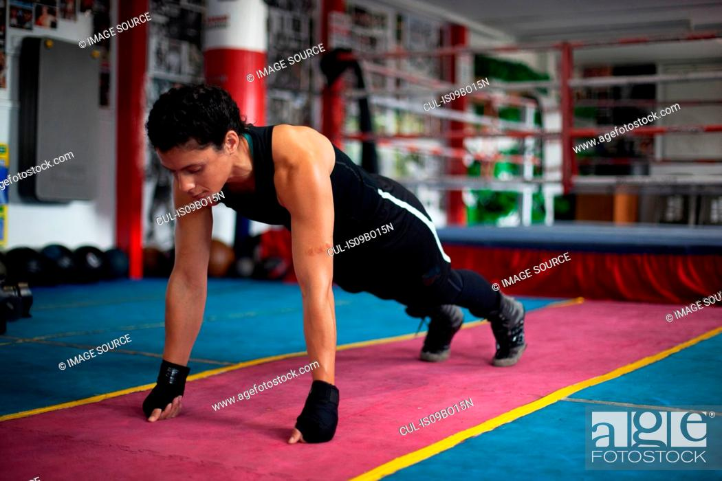 Stock Photo: Female boxer doing planks in gym.