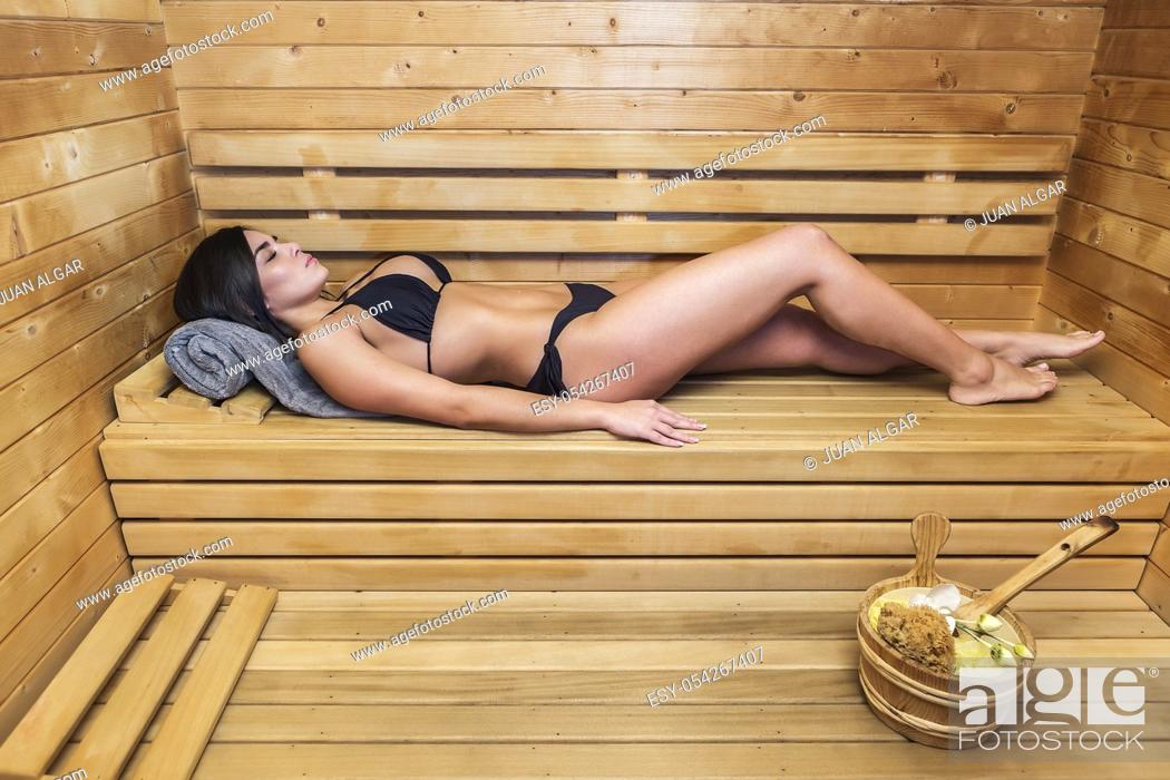 Stock Photo: Young brunette lying alone on wooden shelf in steam room and relaxing.