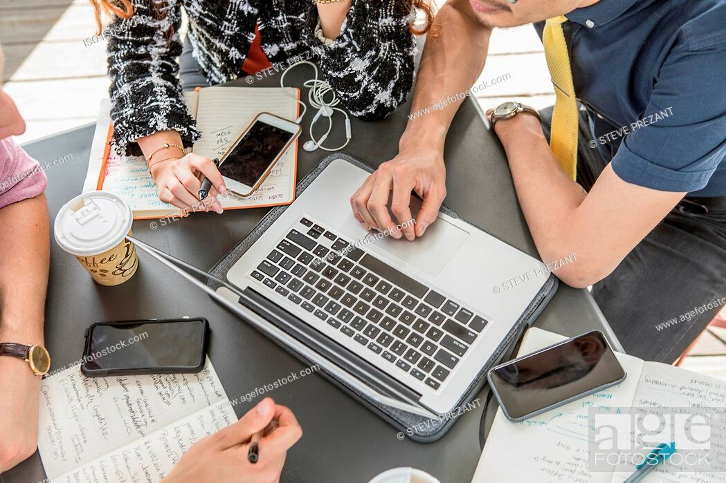 Stock Photo: Cropped shot of business team using laptop at cafe meeting.