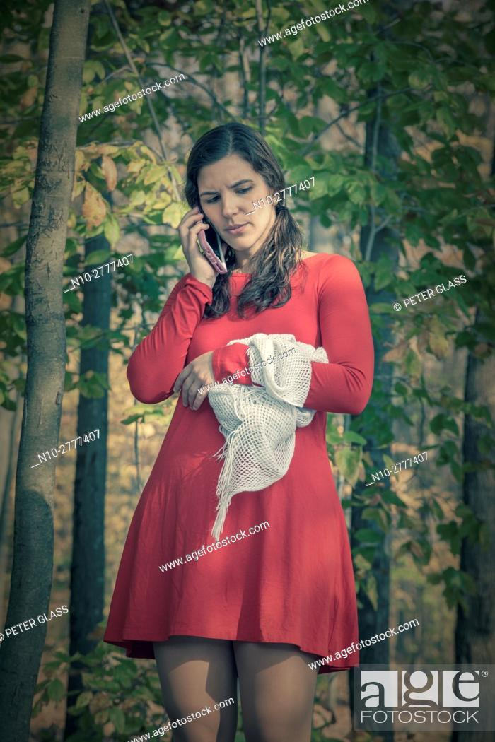 Stock Photo: Young woman in a red dress in the woods during autumn, holding a shawl and talking on her cell phone.