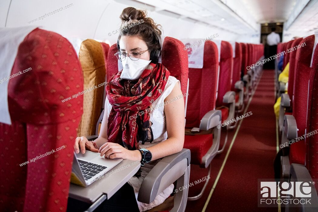 Stock Photo: Young woman wearing a face mask while she works on an almost empty airplane due to the travel concerns and restrictions caused by the Covid-19 pandemic.