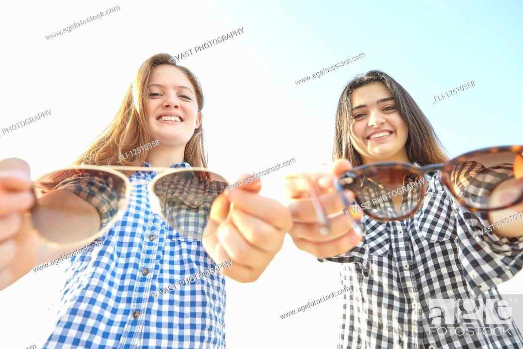 Imagen: Two teenage girls posing and holding out their sunglasses towards the camera as if offering them to the viewer, Woodbine Beach; Toronto, Ontario, Canada.
