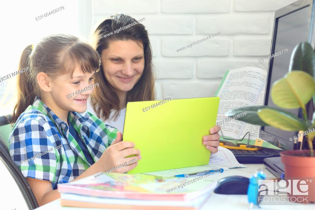 Stock Photo: Mom and daughter communicate via video using a tablet computer.