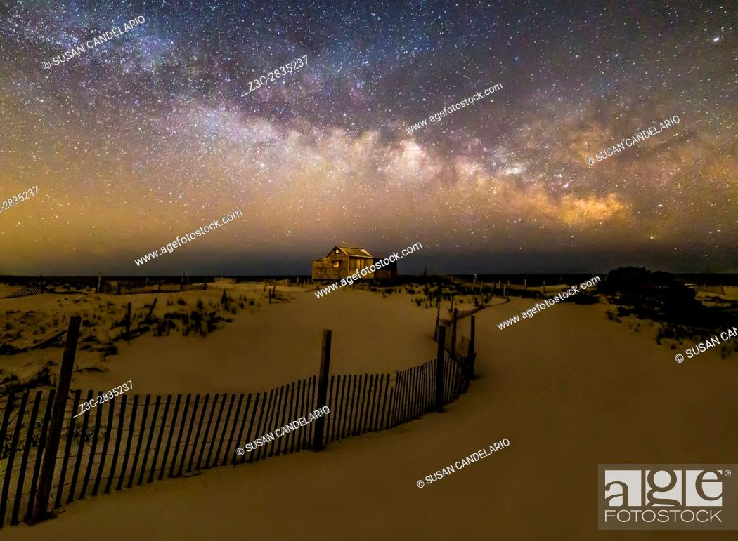 Stock Photo: Jersey Shore Starry Skies and Milky Way - Island Beach State Park at the NJ Shore with beach fences leading to the Judge's Shack underneath a starry sky with.