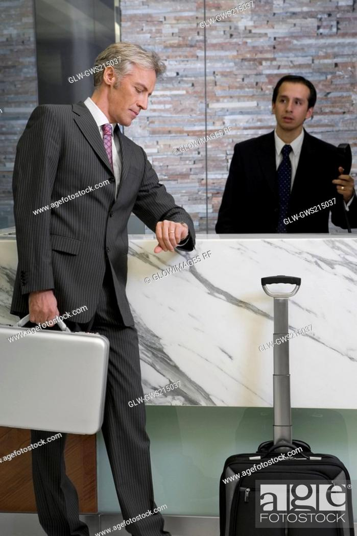 Stock Photo: Side profile of a mature man waiting at the reception and checking the time.