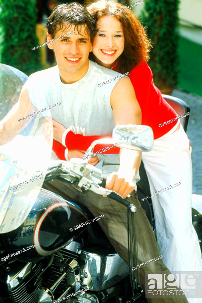 Stock Photo: Portrait of young couple sitting on a motorcycle.