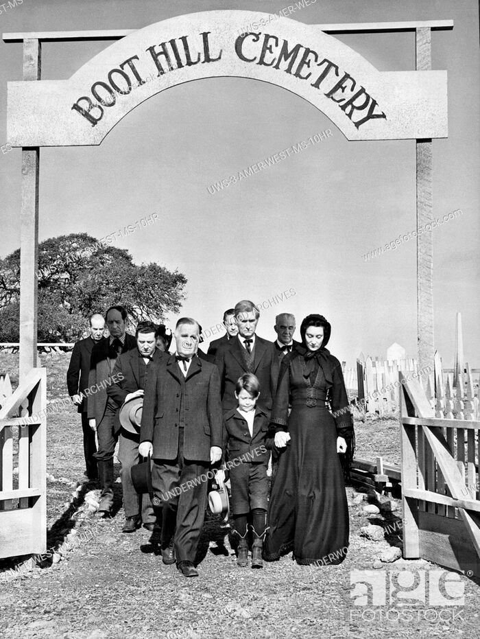 Stock Photo: Hollywood, California: c. 1952.Mourners walking out of the Boot Hill Cemetary in a Western movie scene.