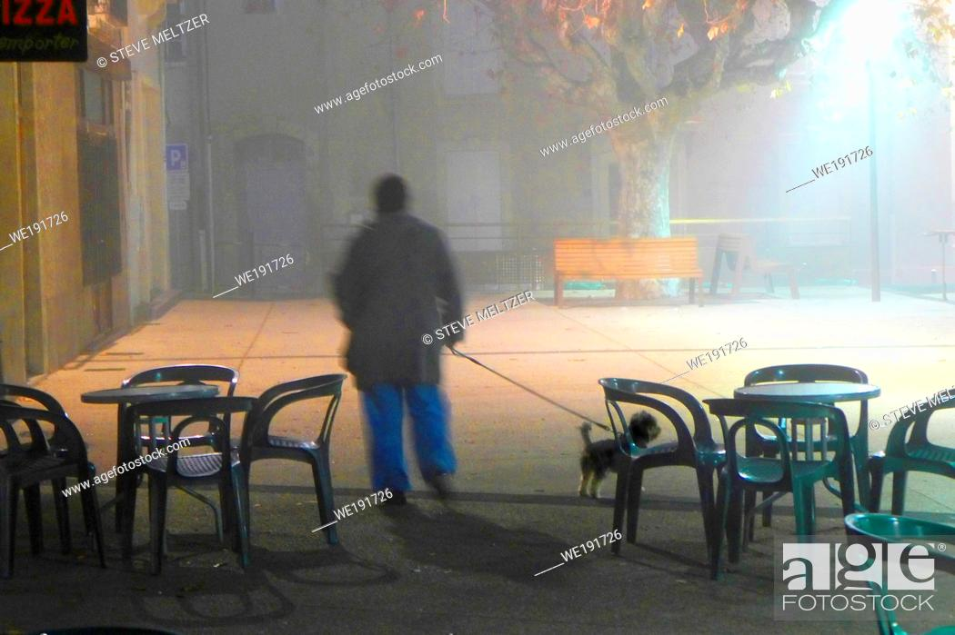 Stock Photo: A woman walks her dog in an early morning fog and dew in Pezenas, France.