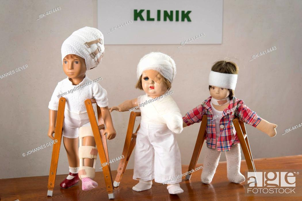 Stock Photo: Three dolls walking with crutches, leg splint, bandages on head, eye patch, arm and shoulder bandage, neck brace, clinic sign behind.