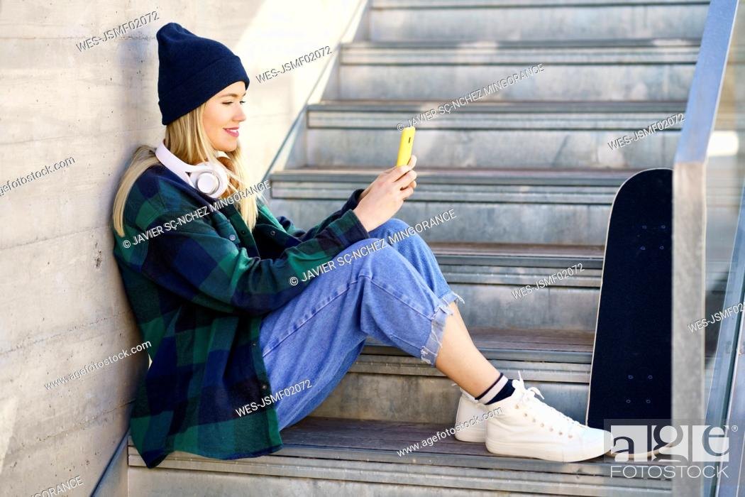 Stock Photo: Smiling woman in knit hat using mobile phone on steps.