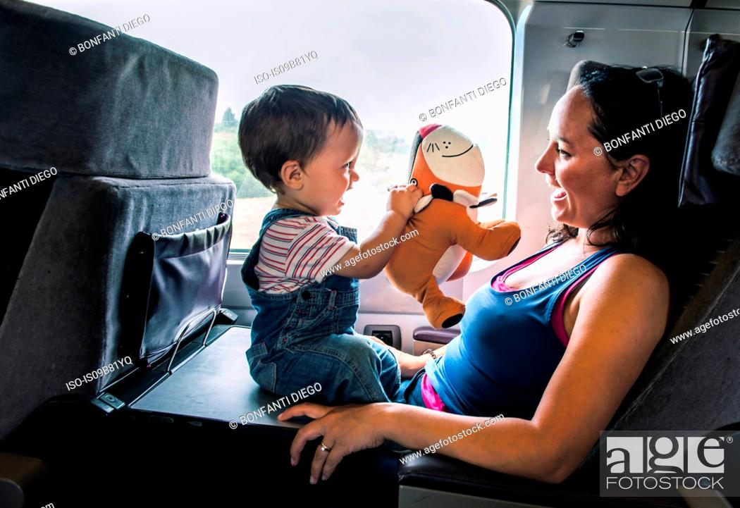 Stock Photo: Mother and young son travelling on train, playing together.