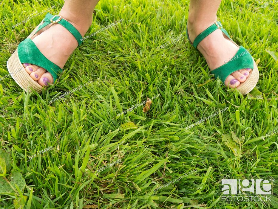 Stock Photo: Woman's feet in green sandals on grass.
