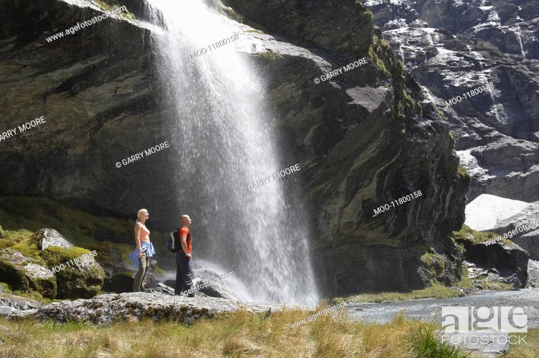 Stock Photo: Hikers standing under waterfall at river.