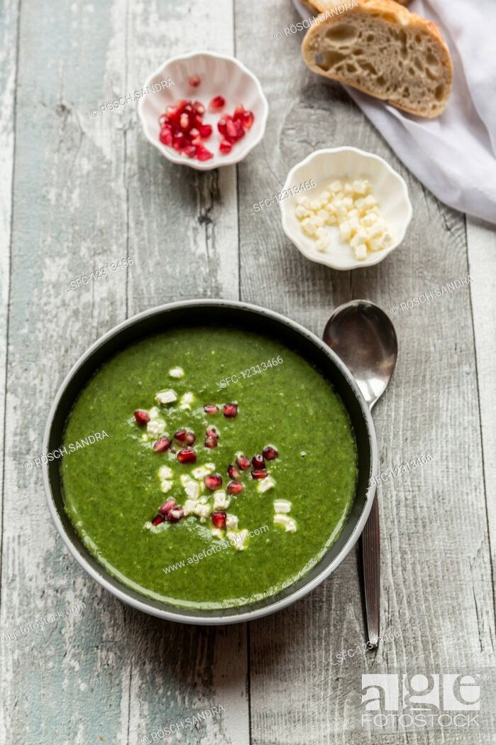 Stock Photo: Green cabbage soup with pomegranate seeds and feta cubes.