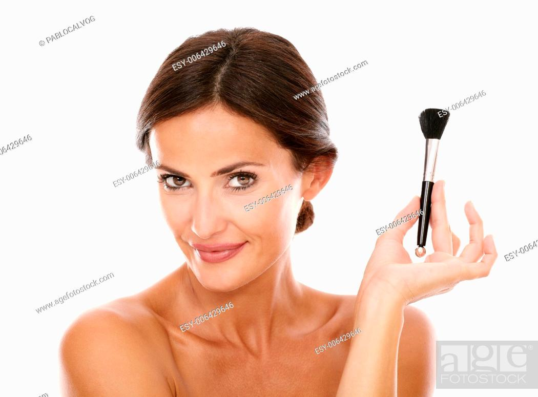 Stock Photo: Smiling hispanic woman with make up brush for smooth her face and nude shoulders while looking at camera on isolated studio.