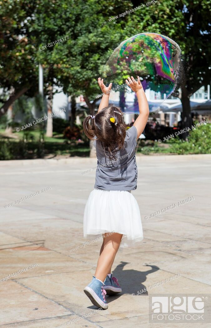 Imagen: Three years old girl playing in the city with a huge bubble.