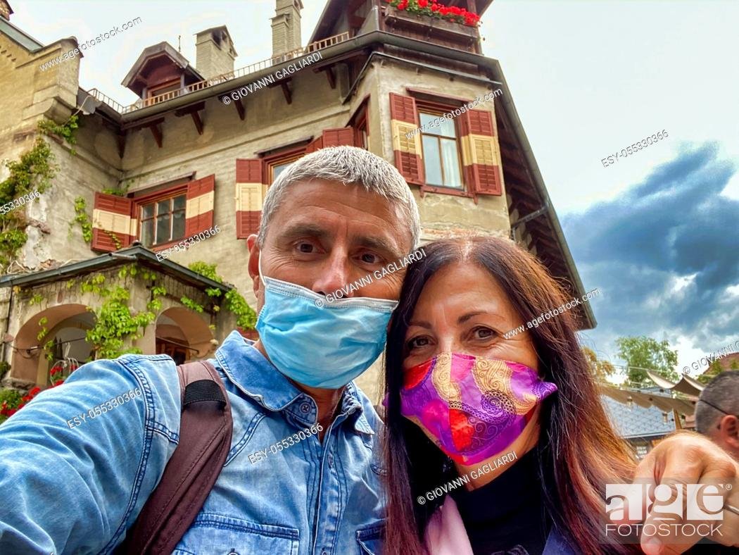 Photo de stock: Couple wearing masks visiting alps town.