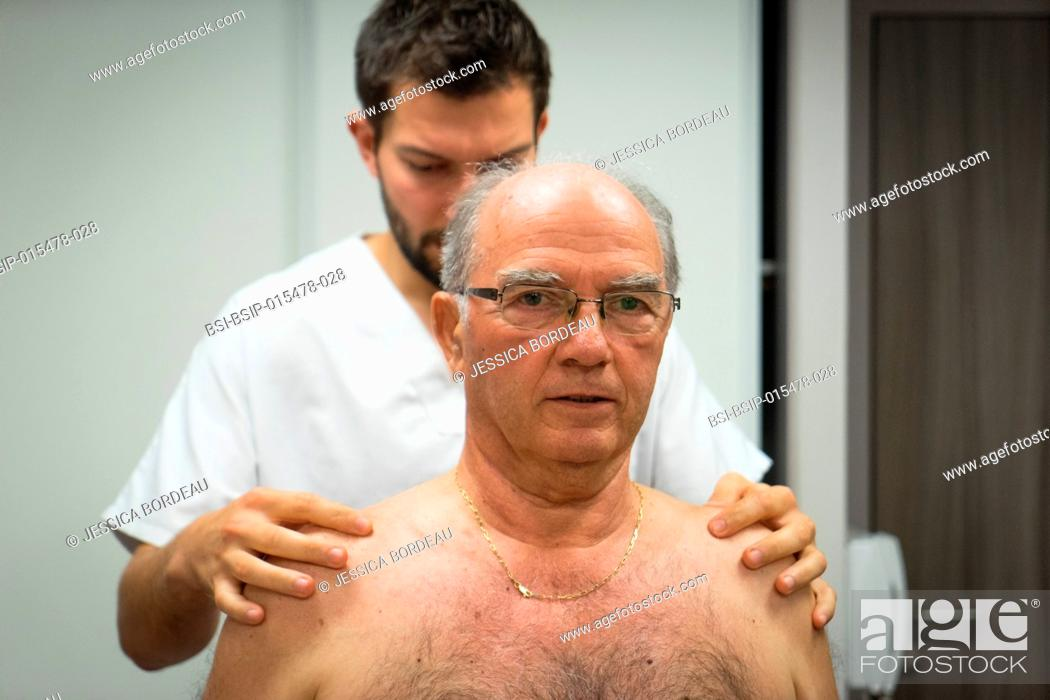 Stock Photo: Reportage in an osteopathy practice in Héyrieux, France. Osteopathy session for a 73-year old man suffering from thoracic block causing strain between the.