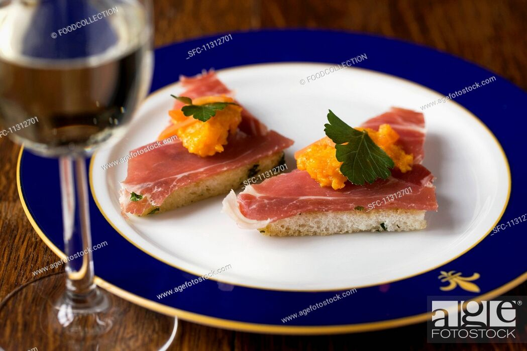 Stock Photo: Toast triangles topped with smoked ham and carrot cream.