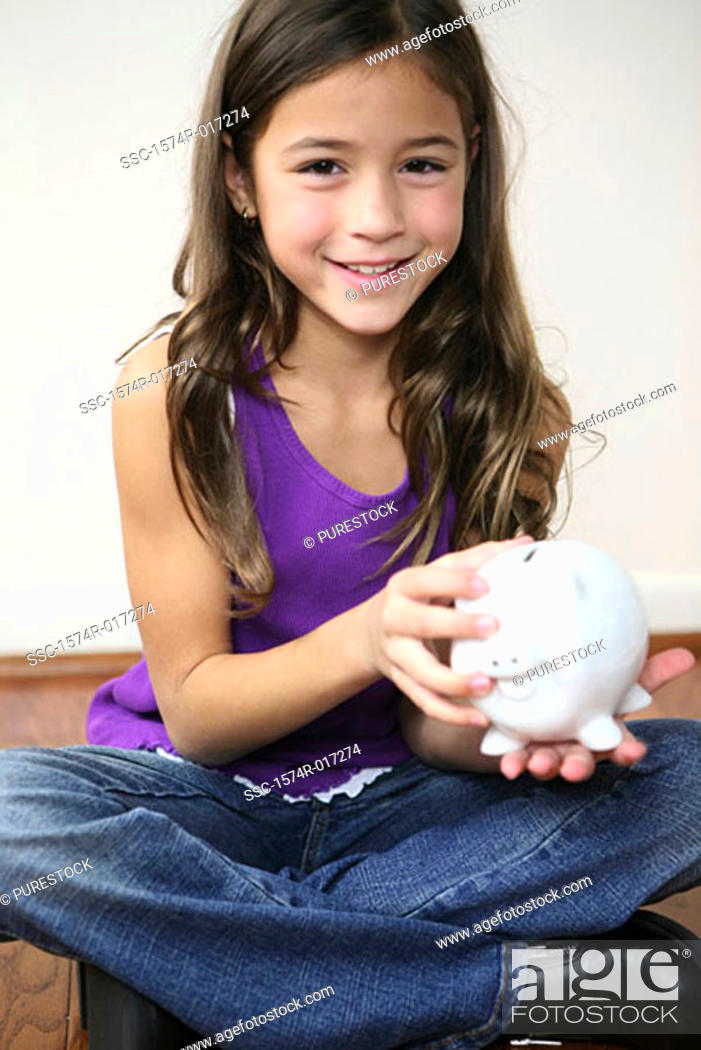 Stock Photo: Portrait of a girl holding a piggy bank.