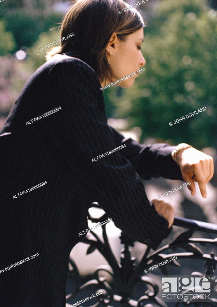 Stock Photo: Woman leaning on balcony railing, looking at watch, close-up.